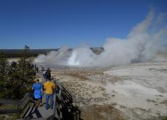 Watching geysers erupt at the Lower Geyser Basin in Yellowstone, on a Yellowstone tour from West Yellowstone, on a beautiful blue sky day.