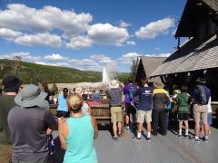 Watching Old Faithful erupt from Old Faithful Inn on a bluebird sky day.