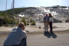 People pose for a picture in front of Roaring Mountain in Yellowstone.