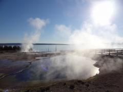 The sun rises over West Thumb geyser basin early in the morning, on a Yellowstone tour from West Yellowstone.